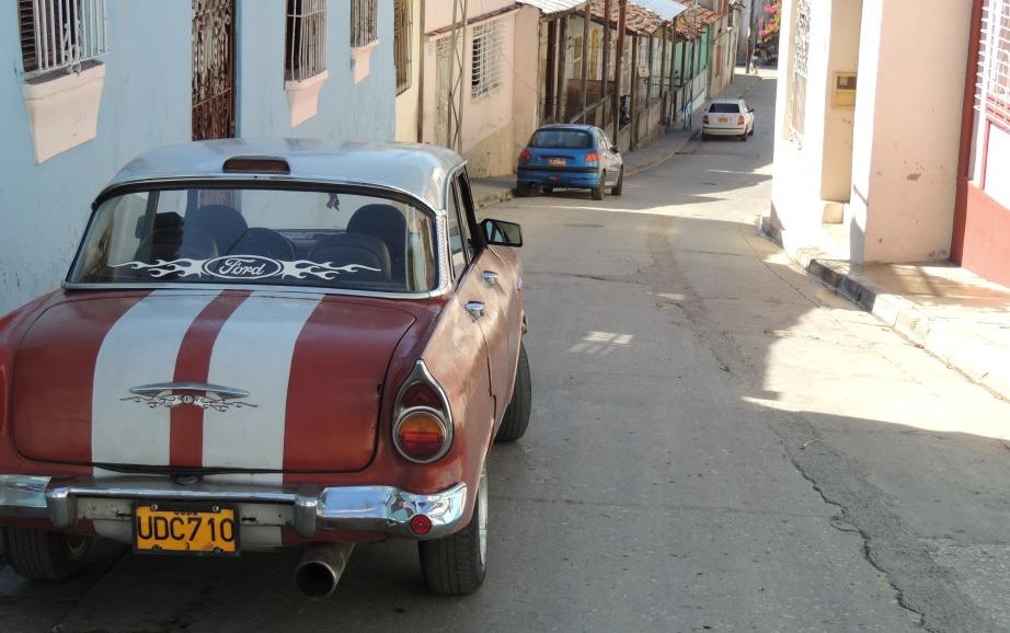 Even verderop zie je onze huurauto staan voor onze casa in Santiago de Cuba. Netjes tegen de rand van de stoep en spiegels ingeklapt. Zoals het hoort.